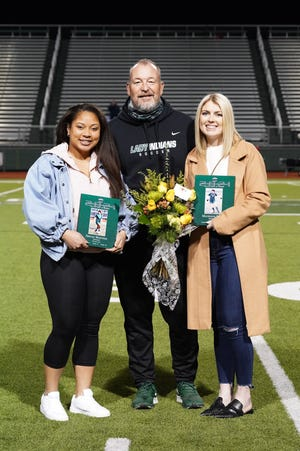 Former Waxahachie soccer players Abigail Martinez, left, and Mackenzie Posey pose with WHS head coach Jason Venable on Tuesday night before the Lady Indians' District 11-6A match with Cedar Hill at Lumpkins Stadium.