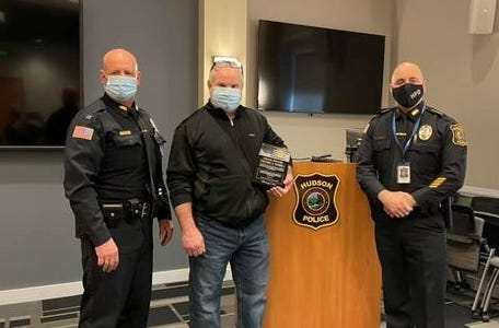Hudson Police Officer Michael Russell, center, retired on Feb. 2 after more than 20 years with the local department. On his last day on duty, Russell was presented with a commemorative plaque by Capt. Chad Perry, left, and Chief Rick DiPersio.