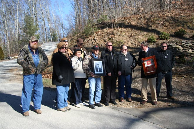 Family members and law enforcement officers gathered at the spot where Sheriff Philip Noland was shot and killed in 1862. Lynn Noland holds the framed rosette; Lindon Nichols holds a portrait of Philip; Sheriff Suttles is to Nichols' left.