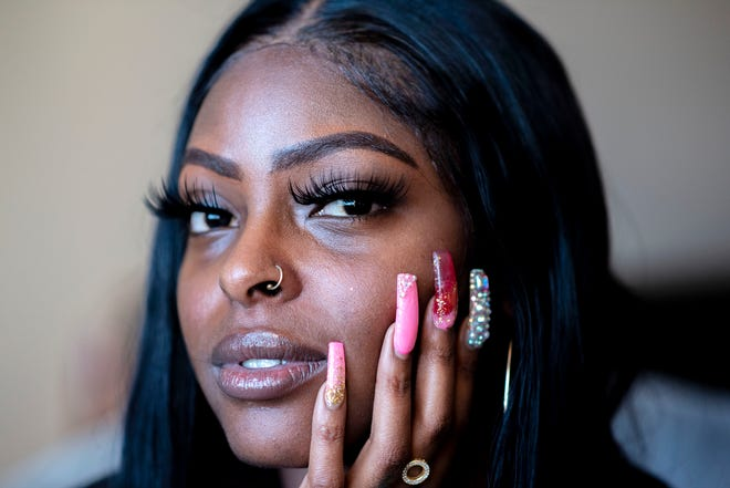 Entrepreneur Darika Marie Williams models her nails and lashes on Tuesday, Feb. 2, 2021 at her apartment in Battle Creek, Mich. When the pandemic hit Michigan, the 25-year-old esthetician focused her energy on launching a line of lip gloss and charm bangles.