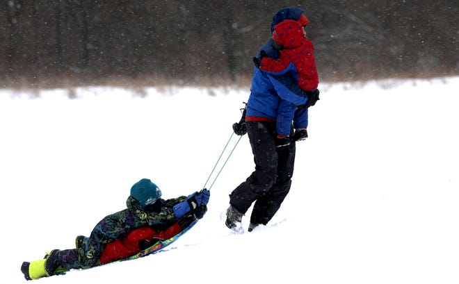 Matt Foss pulls his kids up the sledding hill for their fourth run at Indian Springs Metropark in White Lake, Michigan on February 5, 2021,  This area in Oakland County received 4 inches of new snow added to what was already on the ground.