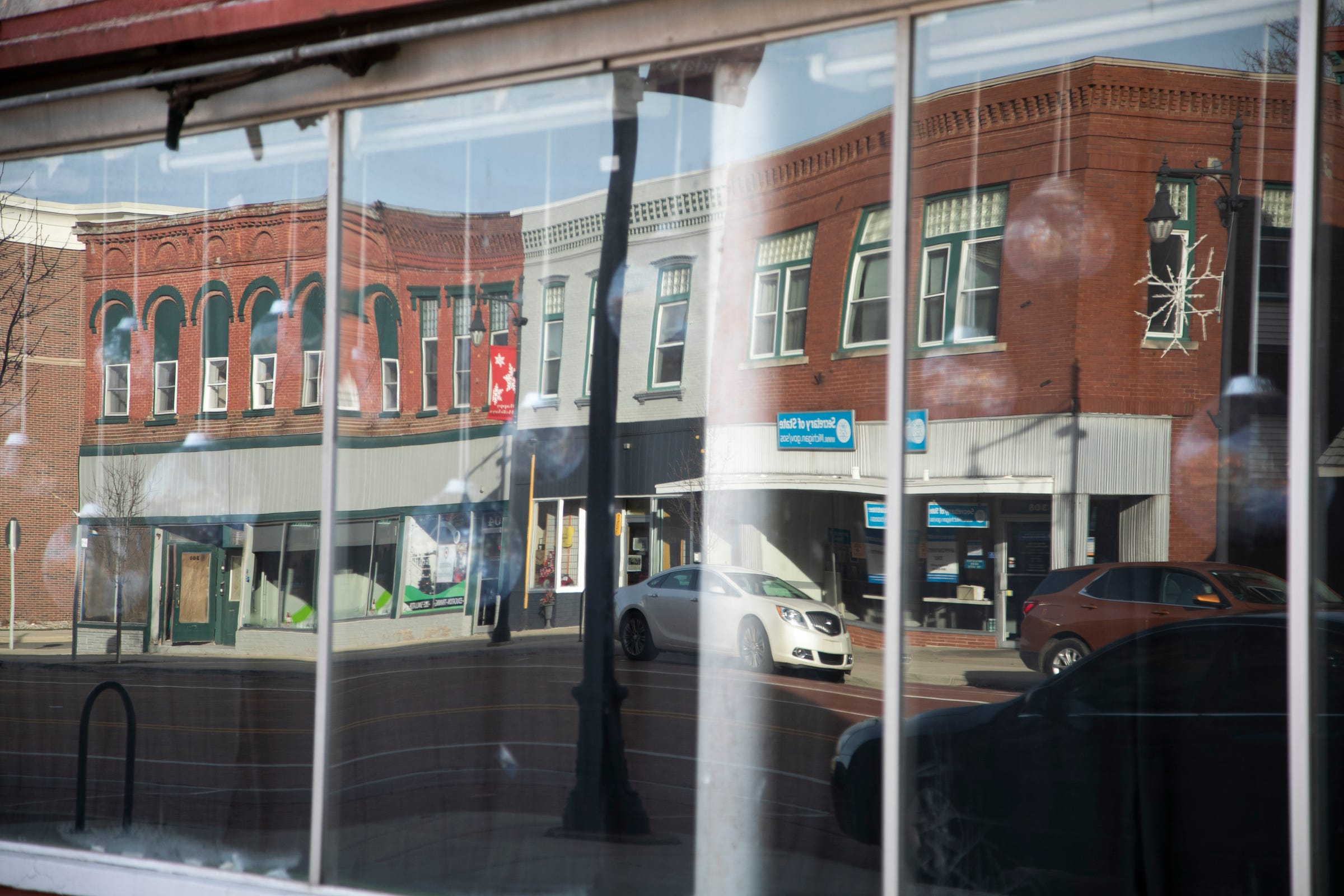 Buildings reflect in an empty storefront on S. Superior Street in December in Albion.