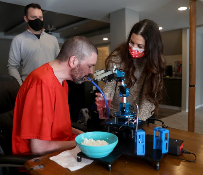 Matt McKeown, a former mechanical engineer diagnosed with ALS in 2017, is helped with drinking water by Cat Nay as her husband and McKeown's best friend Dave Nay looks on in the basement of their Michigan home on Feb. 5, 2021.
