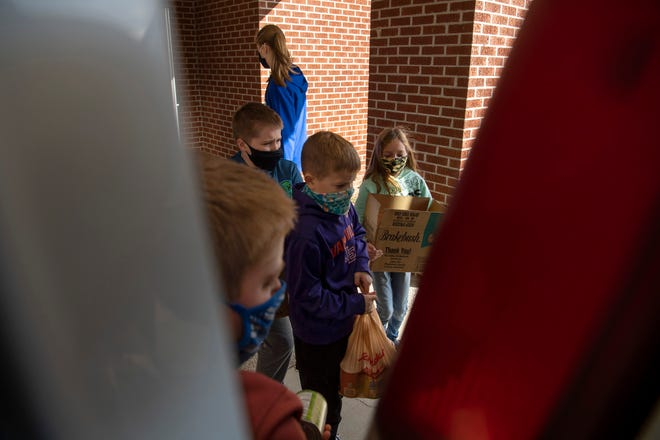 Students at Good Shepherd Catholic School load food and toiletries into a van to be delivered to St. Vincent de Paul Society Food Pantry as part of the school's War on Hunger Project Friday morning, Feb. 5, 2021.