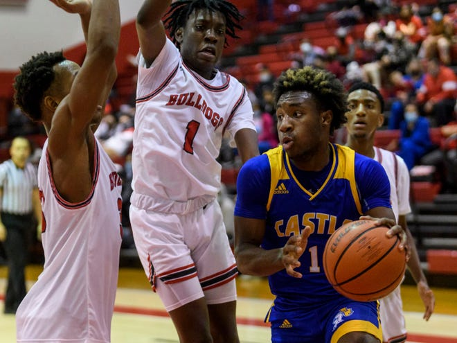 Castle's Isaiah Swope (1) drives around Bosse's Xavier Burton (33) and Jameer Ajibade (1) at Bosse High School in Evansville, Ind., Thursday, Feb. 4, 2021. The Knights defeated the Bulldogs, 62-45.
