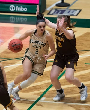 Colorado State Rams guard Tori Williams (2) dribbles around Wyoming Cowgirls guard McKinley Bradshaw (12) in the second quarter of the Rams' home win on Thursday, Feb. 4.