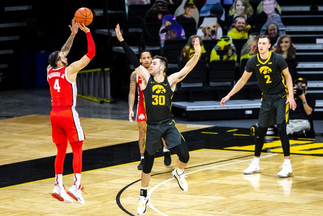 Ohio State guard Duane Washington Jr. (4) makes a 3-point basket as Iowa's Connor McCaffery (30) defends in the second half during a NCAA Big Ten Conference men's basketball game, Thursday, Feb. 4, 2021, at Carver-Hawkeye Arena in Iowa City, Iowa.