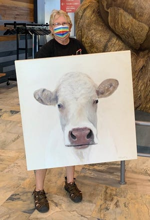 Marla Payne, multimedia artist and December 2020 Lakeshore Technical College welding program graduate, showing her painting, which was on display at Farm Wisconsin Discovery Center.