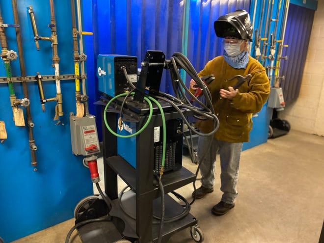 Marla Payne, multimedia artist and December 2020 Lakeshore Technical College welding program graduate, in LTC's welding lab.