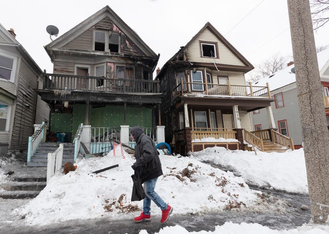 A pedestrian passes by the scene of a fire in the 1900 block of West Burnham Street in Milwaukee on Friday, Feb. 5, 2021. Firefighters spent about 40 minutes battling a heavy fire that spread to three structures.