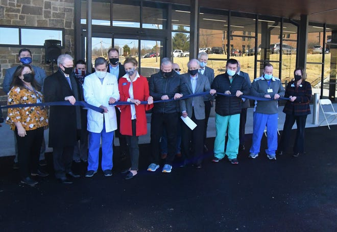 Baxter Regional Medical Center physicians use scalpels to cut through a ribbon at a dedication ceremony for the hospital's new outpatient surgery center.