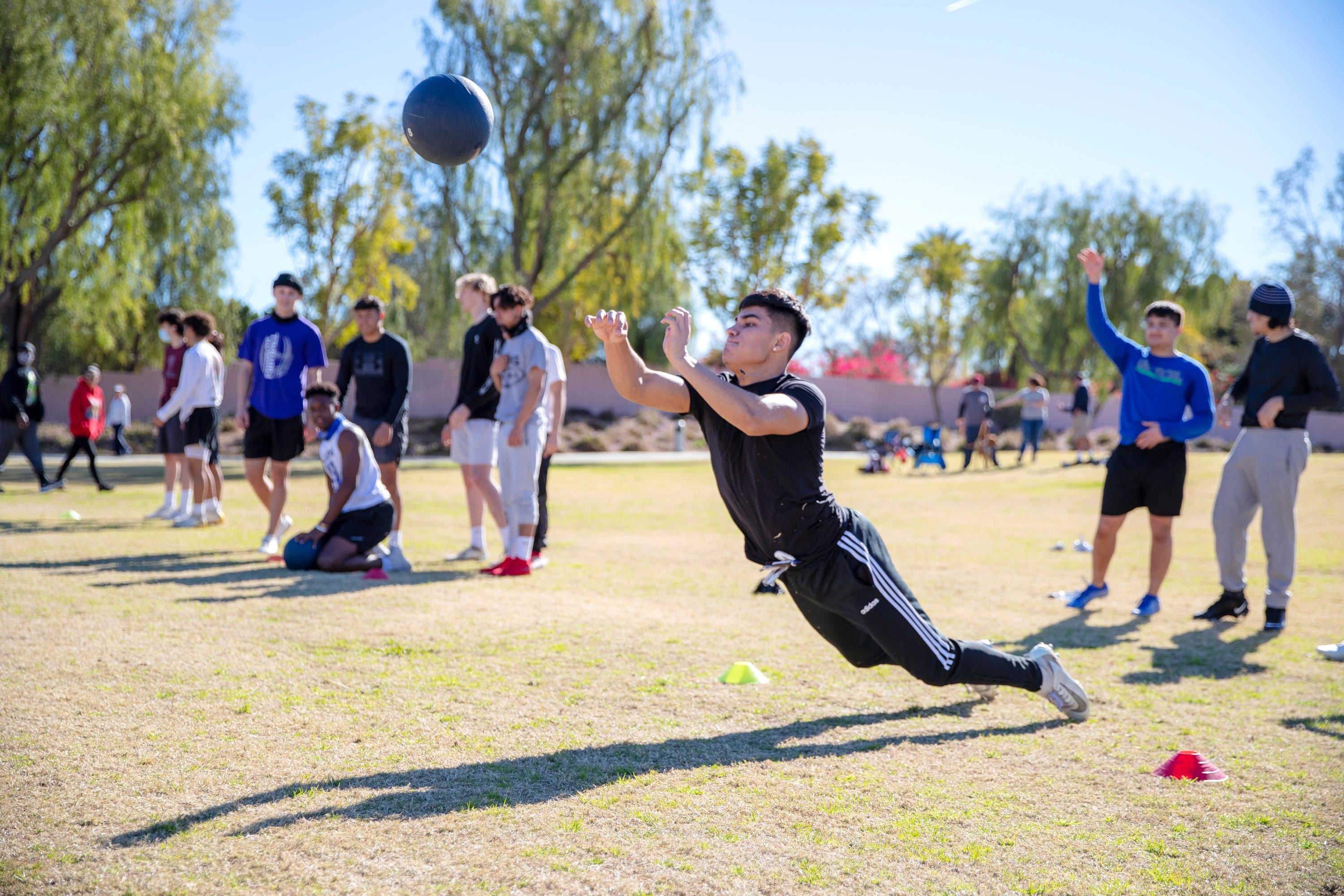 High school athletes throw a medicine ball to gauge explosiveness during a combine exercise during tryouts for the Desert Diablos club football team at La Quinta Park in La Quinta, Calif., on January 30, 2021.