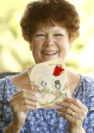 Sandy Mettille poses for a picture with a Valentine's Day card that has been exchanged between her mom and aunt for decades at her home. After both passed away their daughters have now taken up the tradition.
