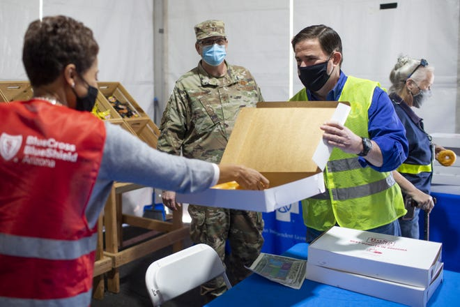 Arizona Gov. Doug Ducey (right) gives out doughnuts to volunteers working to administer COVID-19 vaccinations to people at State Farm Stadium in Glendale on Feb. 5, 2020.