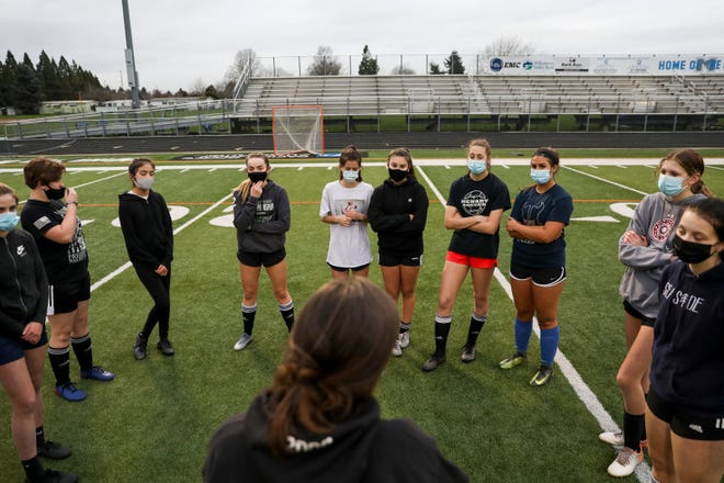 McNary High School girls soccer coach Lauren Brouse huddles with the team after practice on Thursday, Feb. 4.
