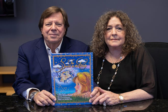 """Ron Sachs and Gay Webster-Sachs with their book """"The Secret in the Clouds"""""""