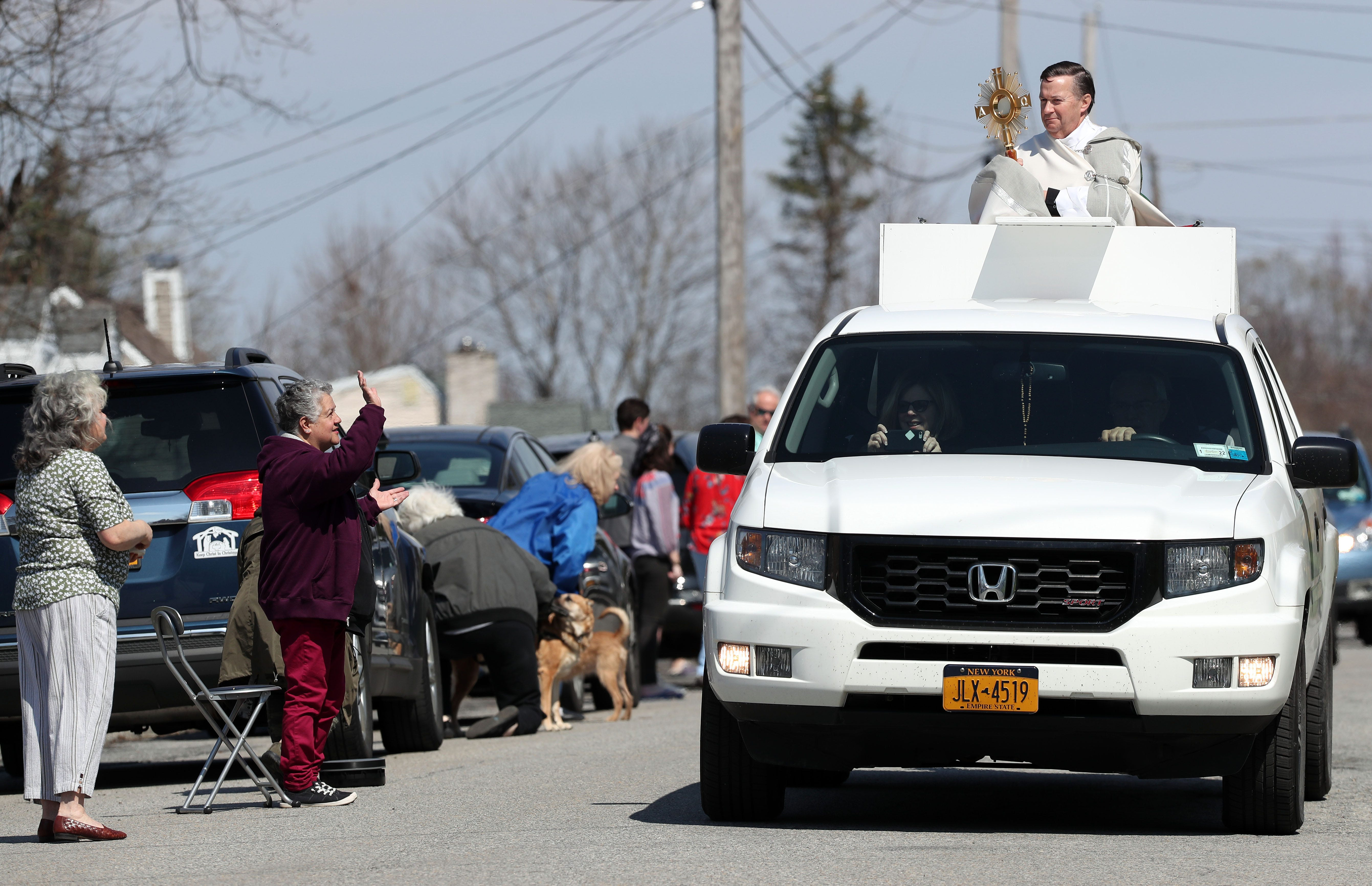 Spiritual leaders took creative measures to mark the holiest days of the year. Saint Lawrence O'Toole Church's pastor, Rev. Richard Gill, is shown here riding in the back of a big SUV in Brewster on Easter Sunday, blessing those who line the streets.