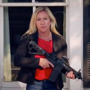"""Rep. Marjorie Taylor Greene holding an assault rifle in a campaign ad from June 2, 2020, in which she tells ANTIFA to """"stay the hell out of northwest Georgia."""""""