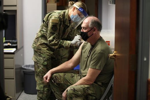 Kansas Air National Guard Maj. Cortney Neblett, left, gives a COVID-19 vaccine shot to Master Sgt. Thomas Lafountain, right, during a clinic for Kansas National Guard personnel, Friday, Feb. 5, 2021, at Air National Guard's base south of Topeka, Kan. The Kansas National Guard received 1,100 doses from the U.S. Department of Defense.