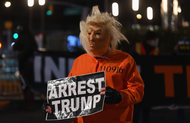 A man dressed as Trump in a prison jump suit protests in front of Trump International Hotel & Tower in New York on Jan. 6, 2021.