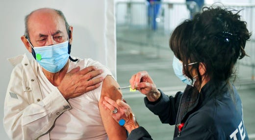 Maximo Michua, 74, holds his sleeve as Kathryne Acuna (R), Director of Ambulatory Clinical Services at Kaiser Permanente, administers his Covid-19 vaccine on the opening day of a large-scale Covid-19 vaccination site at a parking structure at Cal Poly Pomona University in Pomona, California on February 5, 2021.