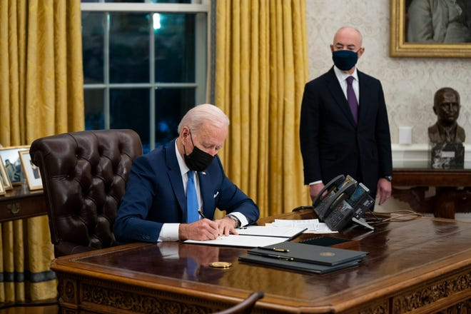 Secretary of Homeland Security Alejandro Mayorkas looks on as President Joe Biden signs an executive order on immigration, in the Oval Office of the White House, Feb. 2, 2021, in Washington.
