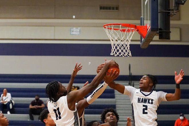 Ke'shawn Williams, right, and other Hawks battle for the ball in a 79-71 win over Manor on Friday. Williams had 36 points in the crucial District 18-5A game.