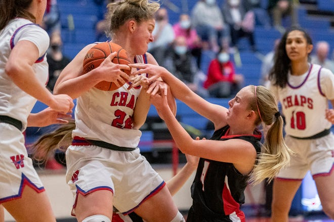 Westlake forward Gwen Gilmore, left, and Lake Travis guard Peyton Ferrell battle for the ball during a District 26-6A high school basketball game at Westlake High School on Friday.