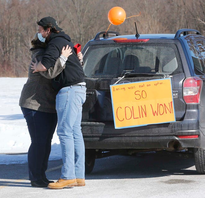 Colin Bowser, right, hugs his pastor, the Rev. Sandy Phillips of Oak River Church of Solon during Bowser's surprise reverse drive-thru party at Liberty Park in Twinsburg. Bowser rang the bell to celebrate his final treatment for acute lymphoblastic leukemia two days earlier.