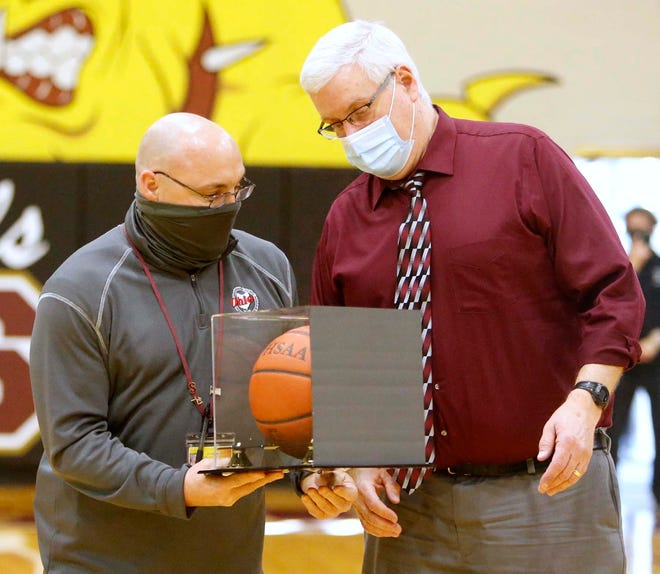 Stow Athletic Director Cyle Feldman presents boys basketball coach Dave Close with the game ball after his 600th win, a 46-36 victory over Nordonia on Saturday at Stow-Munroe Falls High School. [Karen Schiely/Beacon Journal]