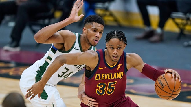 Cavaliers' Isaac Okoro (35) works against Milwaukee Bucks' Giannis Antetokounmpo (34) during the second half of an NBA basketball game Friday, Feb. 5, 2021, in Cleveland. (AP Photo/Tony Dejak)