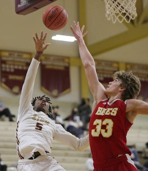Stow's Marvin Campbell, left, makes a layup over Brecksville's Chase Garito during the second half of the Bees' 63-58 overtime win Friday night in Stow. [Jeff Lange/Beacon Journal]