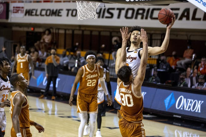 Oklahoma State guard Cade Cunningham shoots a layup over Texas forward Brock Cunningham during the first overtime of the Cowboys' victory Saturday.