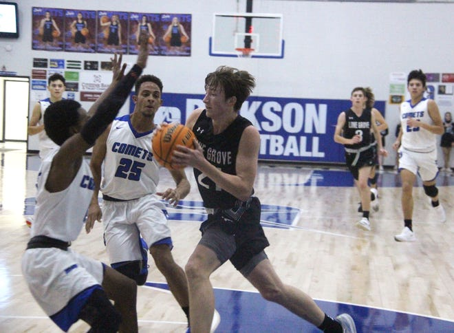 Lone Grove's Jeshua Miller drives to the hoops as Dickson's  Johnny Smith (25) and Jzavionn Bennett on Friday night. Miller led the Longhorns with 16 points in a 46-38 win.