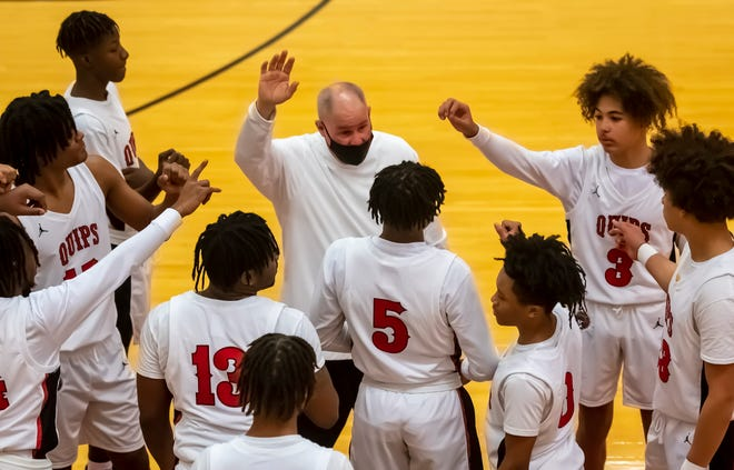Aliquippa High School boys basketball players surround head coach Nick Lackovich before they head onto the court at the start of the third quarter against Freedom Friday at Aliquippa High School.