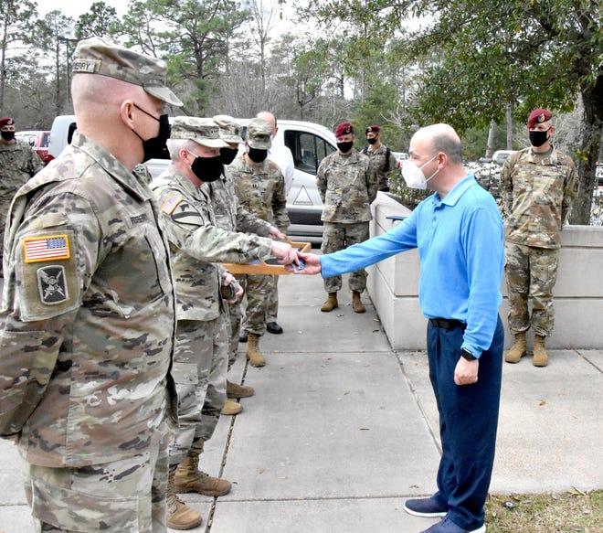 Lt. Gen. Douglas Gabram (left), Commanding General, U.S. Army Installation Management Command, hands coins to Fort Polk IMCOM employees for their exemplary work, Jan. 26.