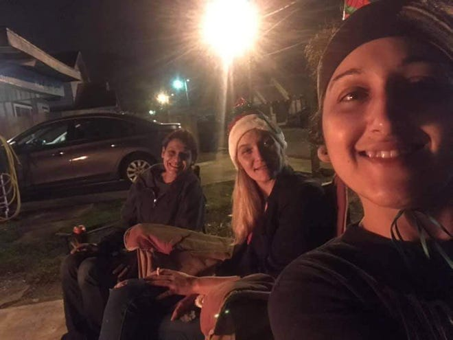 From left, Monica Parfait, Brittany Cormier and Gabby Pellegrin relax by a fire.