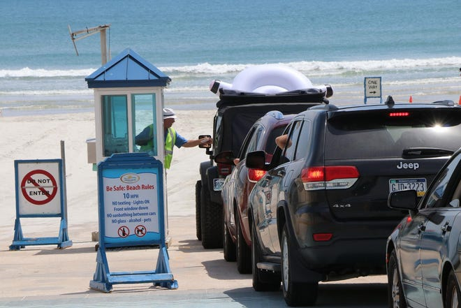 Cars stop to pay toll before driving on to Volusia beaches