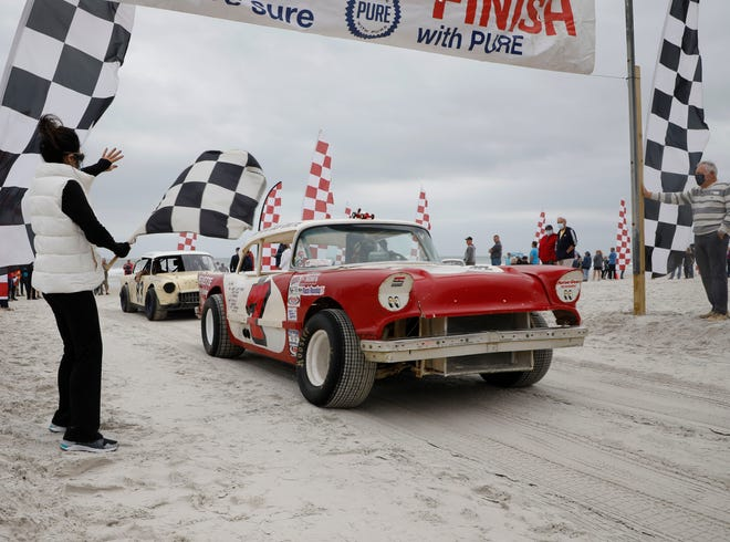 The checkered flag waves as old race cars drive toward the North Turn Exit while fans wave at the driver during the 10th annual North Turn Legends Parade on Saturday, Feb 6, 2021, in Ponce Inlet.