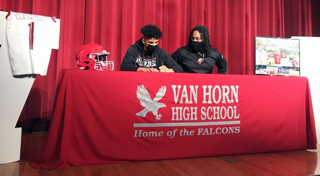 Sean Mitchell shares the stage at Van Horn High School with his football coach William Harris as he signs his national letter of intent to play football at William Jewell College Friday.