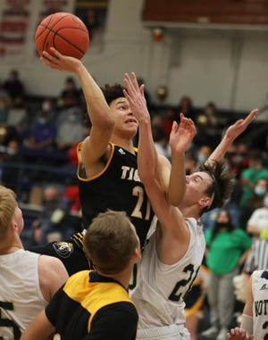 New London Blaise Porter (21) goes up for a basket while guarded by Josh Smith (20) during their game against Notre Dame High School, Friday Feb. 5, 2021 at Notre Dame's Father Minett Gymnasium.