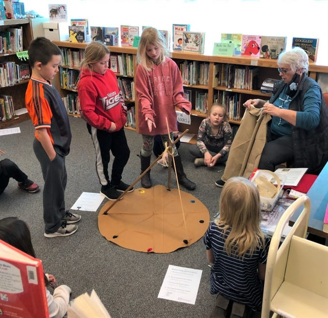 The Kansas Day Celebration provided a demonstration in constructing a teepee with Mrs. Kristi Mettlen (far right) and third grade students (L-R): Gage Makings, Maysa Pagura, Elle Lyle, Hadley Bland (sitting), and Sydney Schultz (lower right).