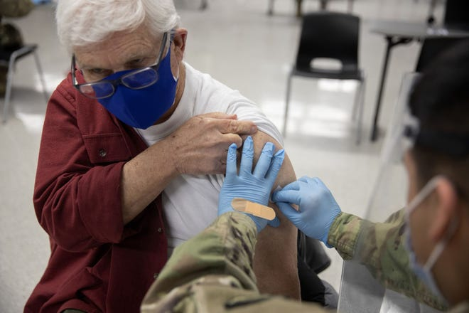 Gerald Lewis, 82, gets a Pfizer COVID-19 vaccine at Triton College in River Grove on Feb. 4, 2021. The Illinois National Guard helped Cook County set up a mass vaccination site and expect to do about 600 vaccines a day.