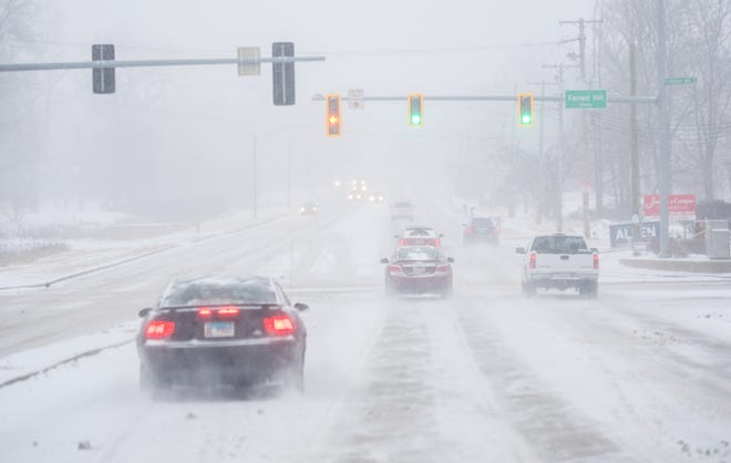 Drivers make their way up Knoxville Avenue as a steady snowfall covers the road and limits visibility Saturday, Feb. 6, 2021 in Peoria.