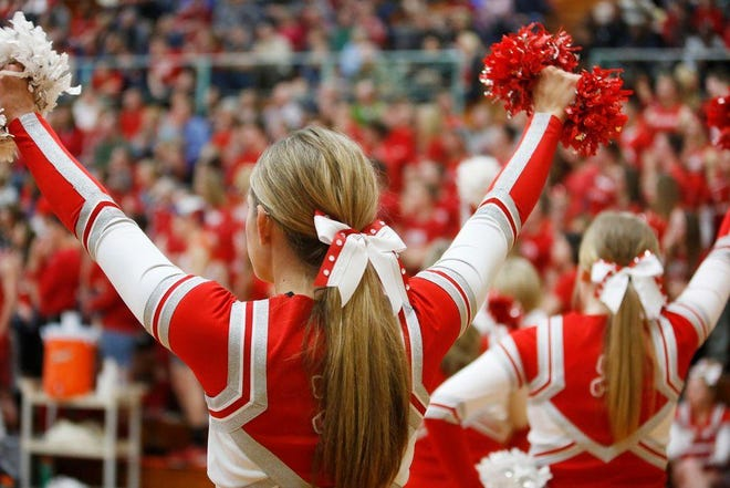 Morton cheerleaders stand on the sidelines during a basketball game.