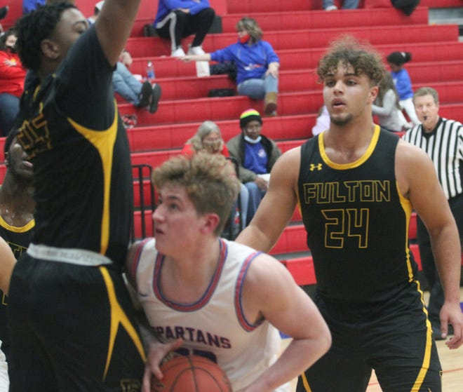 Moberly Spartan junior Brendan Milcik looks for a way to put up a shot Friday while being fronted by Fulton's Colby Lancaster with Josh Reams (#24) assisting Lancaster from behind. Milcik came off the bench to drain five 3-pointers and score 19 points during Moberly's 68-53 home loss to Fulton.