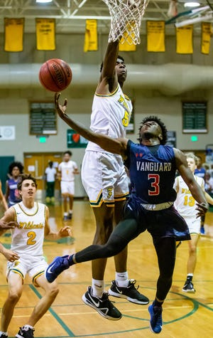 Vanguard's Aaron James drives to the basket for a layup in the first half while being defended by Forest's Brenen Lorient. The Knights defeated the Wildcats, 61-42 Friday night.
