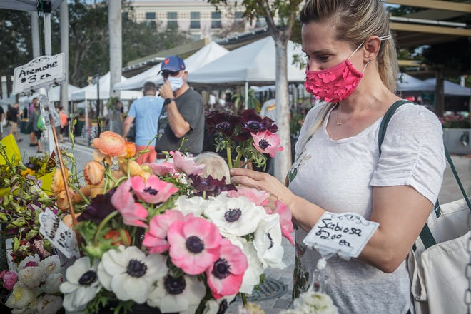Krystal Nodland of West Palm Beach selects flowers at the West Palm GreenMarket last season. The market returns to the downtown waterfront commons Saturday, Oct. 2.
