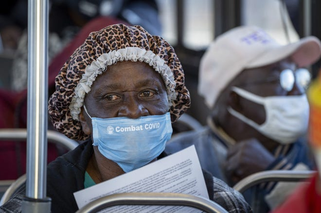 A Belle Glade senior holds on to her paperwork before receiving a COVID-19 vaccine at a vaccination site at Anquan Boldin Stadium in Pahokee on Wednesday. GREG LOVETT / PALM BEACH POST