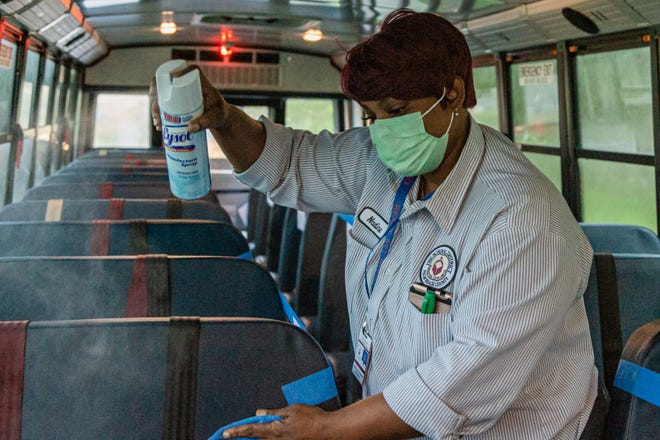 Palm Beach County School bus driver Nadine Cousins sanitizes the seats of her school bus after dropping off students at Lincoln Elementary School in Riviera Beach in September. JOSEPH FORZANO / PALM BEACH POST